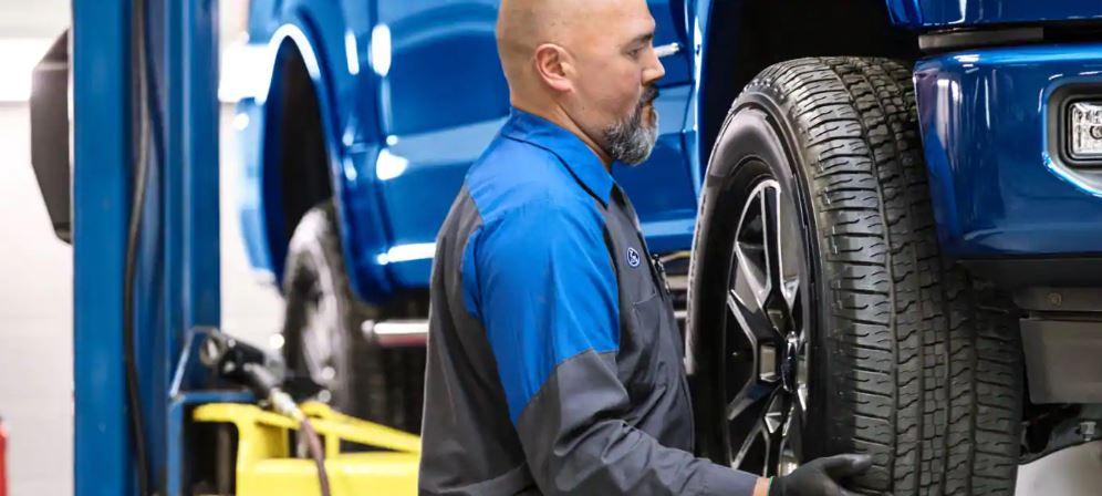 Ford Service Technician Replacing Tire