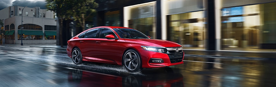 New red Honda Accord driving through the city in the rain