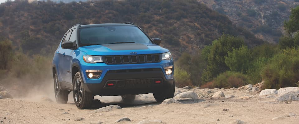 A blue 2019 Jeep Compass offroading over a rocky path