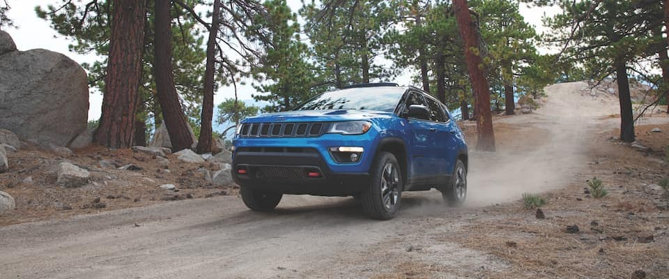 A blue 2019 Jeep Compass on a dirt trail in the forest