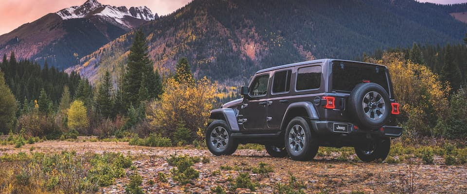 A Jeep Wrangler parked in front of mountains