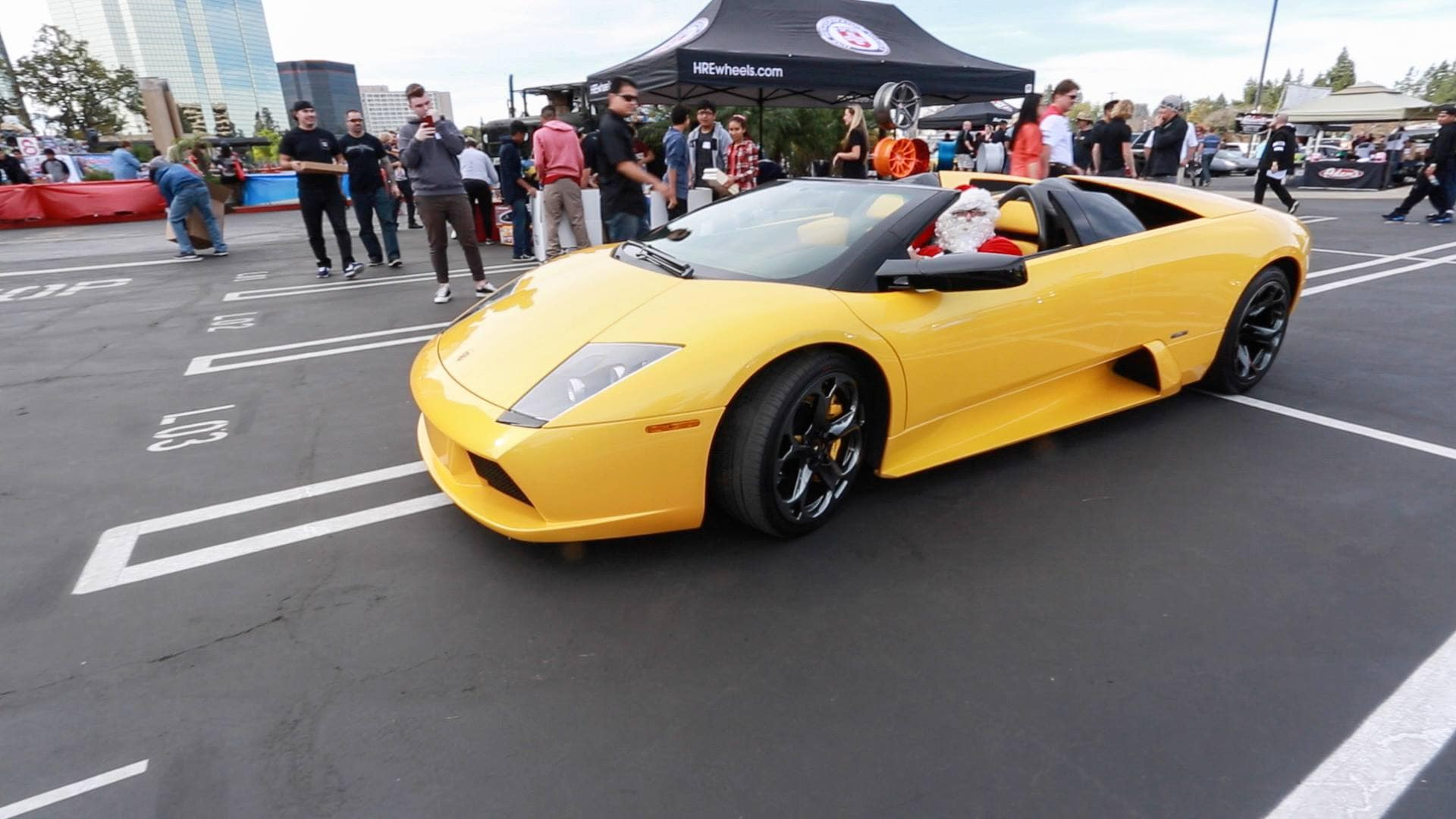 Santa Clause driving a Lamborghini to deliver toys for the kids at Motor 4 toys charity event