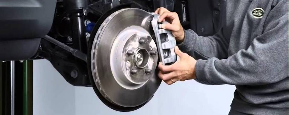 Land Rover technician performing brake service