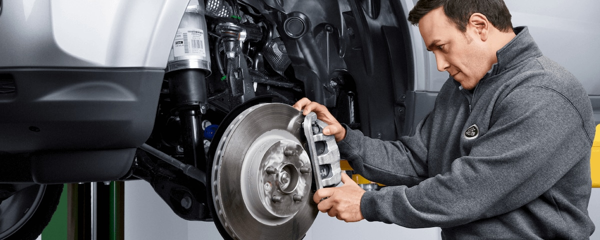 Land Rover service technician performing a brake repair