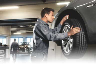 BMW technician performing a wheel alignment