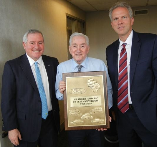 Len Stoler Holding Award at dealership