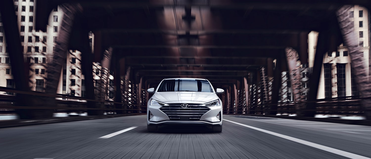 white 2019 Hyundai Elantra driving head-on on a city bridge