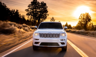 white Jeep Grand Cherokee driving towards camera with headlights on