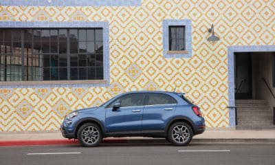 Blue Fiat 500X parked against a patterned yellow wall