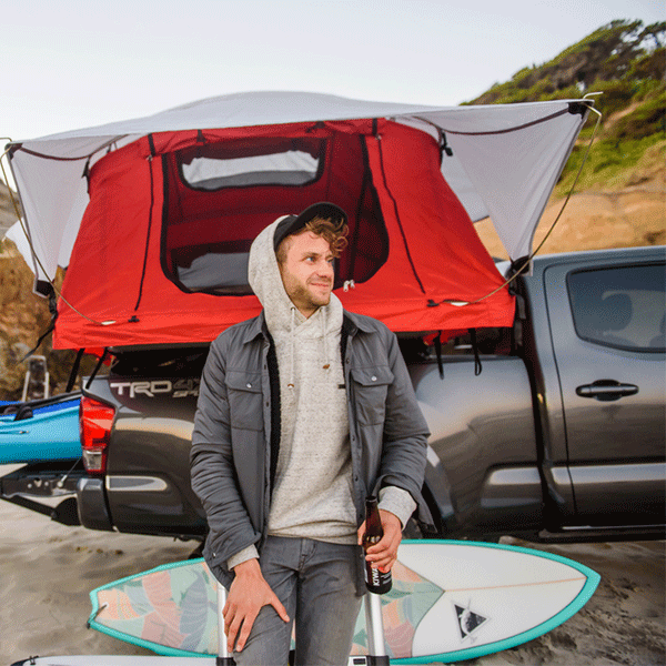 Young man smiling next to his Toyota Tacoma featuring a Yakima Truck Bed Tent, Yakima Racks with bottle openers, Yakima Kayak straps and Rack and Yakima Surfboard Rack