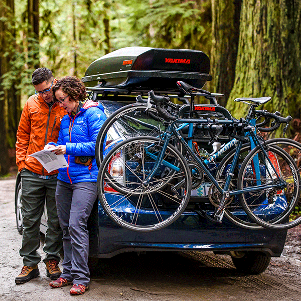 Hikers look at a map next to their Toyota Prius with a Yakima hitch bike rack and Yakima Covered Roof pod
