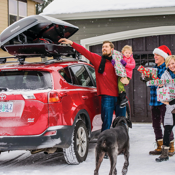 Family in sweaters loading Christmas Presents into a Yakima Covered Cargo pod on top of a Toytoa Highlander