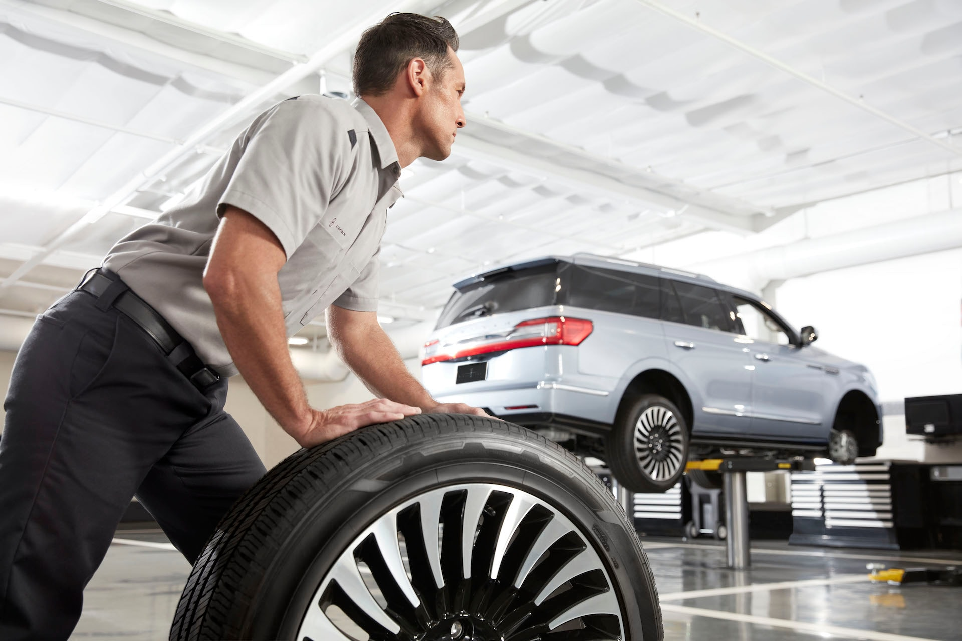How to check your tires' health at Lincoln of New Bern | Lincoln service technician moving tire in Lincoln service center