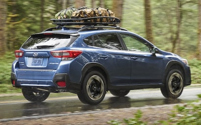 A 2021 Crosstrek with roof rack accessory on its raised roof rails drives down a rough road in the wilderness.