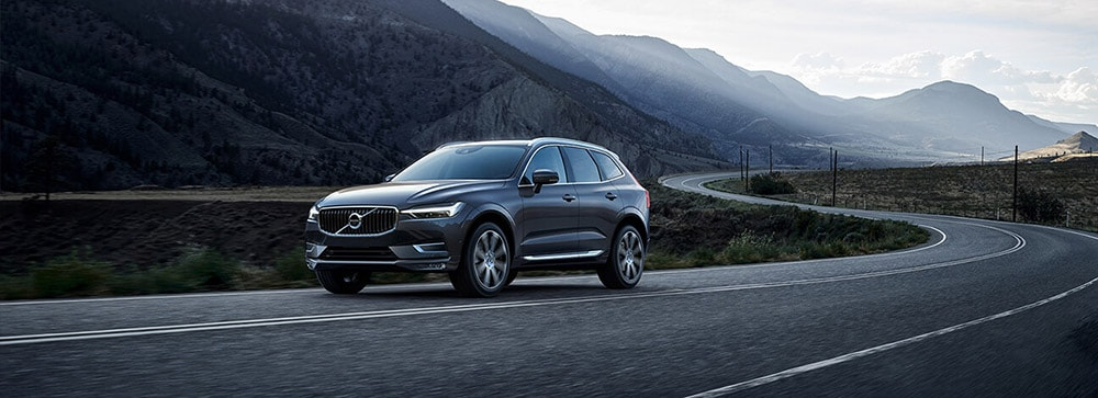 2018 Volvo XC60 driving by mountains