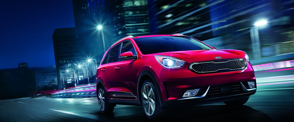 Red Kia Niro driving through city at night