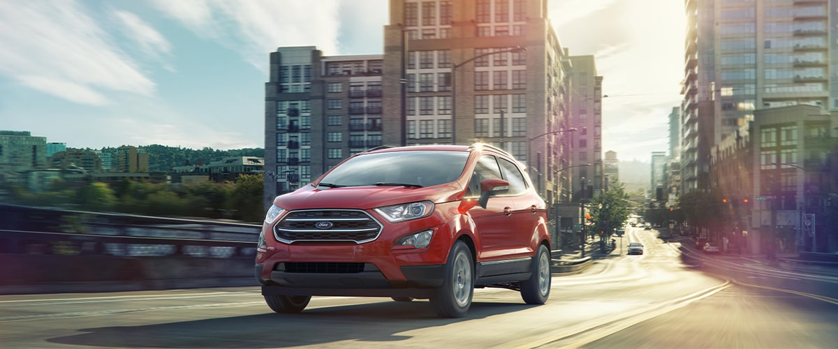 Red Ford EcoSport driving through a city