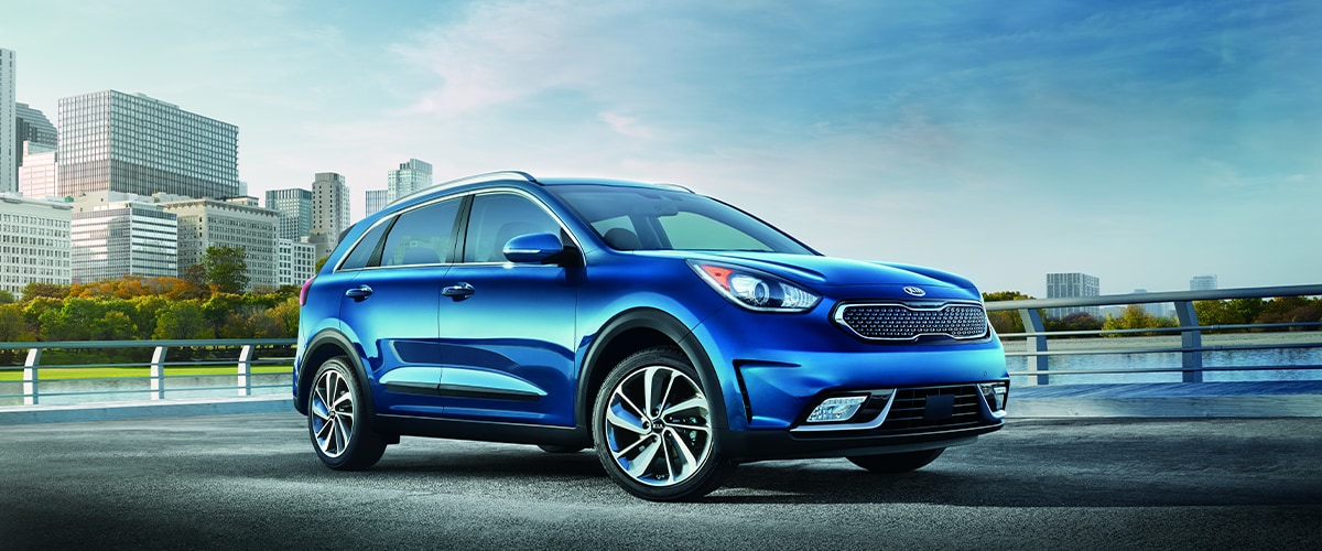 Blue Kia Niro parked in front of city skyline