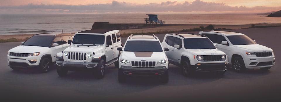 The 2018 Jeep SUV lineup in white parked by the beach at sunset