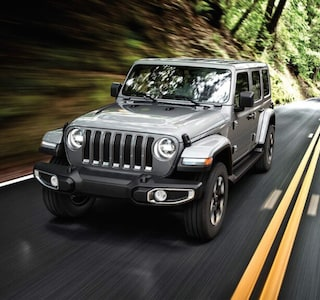 A silver 2019 Jeep Wrangler driving through a woods road
