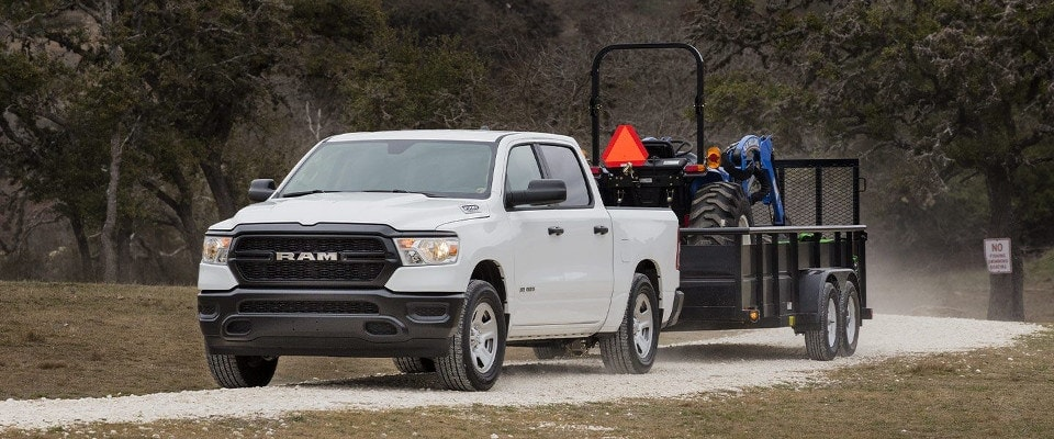 A white 2019 Ram 1500 towing a trailer of equipment