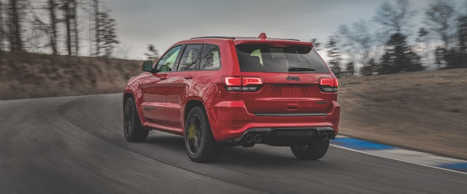 A red Jeep Grand Cherokee driving down an open track