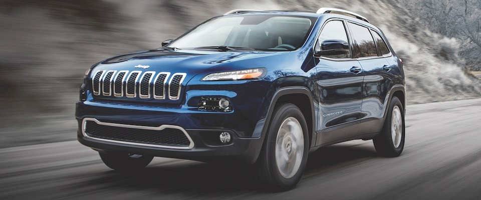 A blue 2019 Jeep Cherokee driving down a road