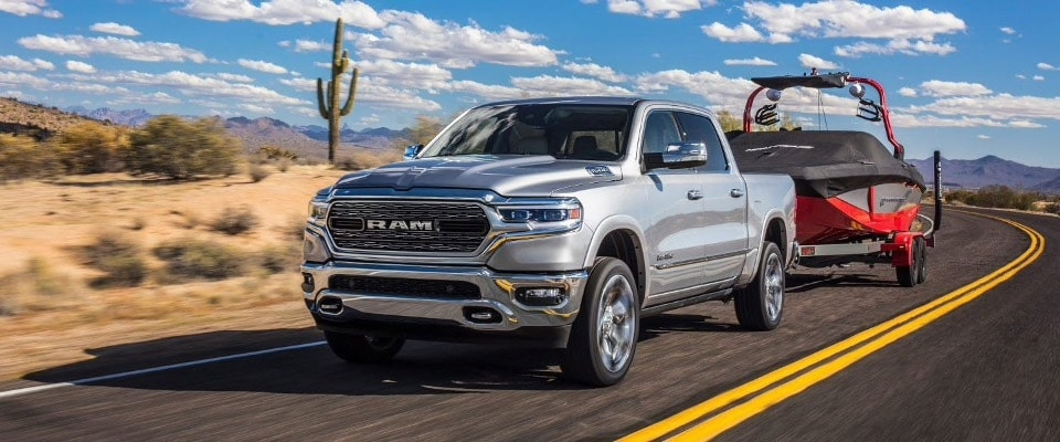 A silver 2019 Ram 1500 towing a boat down an open road