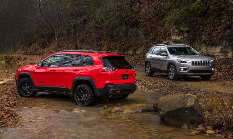Two Jeep Cherokees off roading by a stream