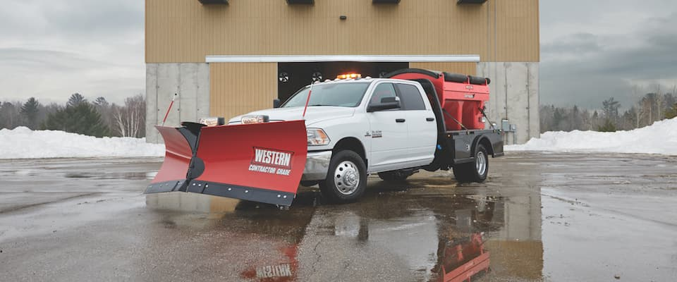 A white Ram 3500 with a snow plow and salt containers