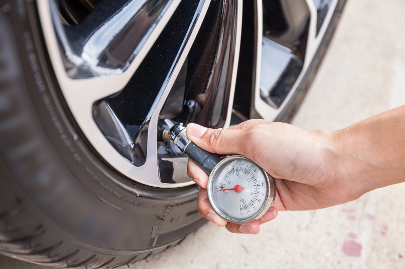 Checking tires with pressure gauge.