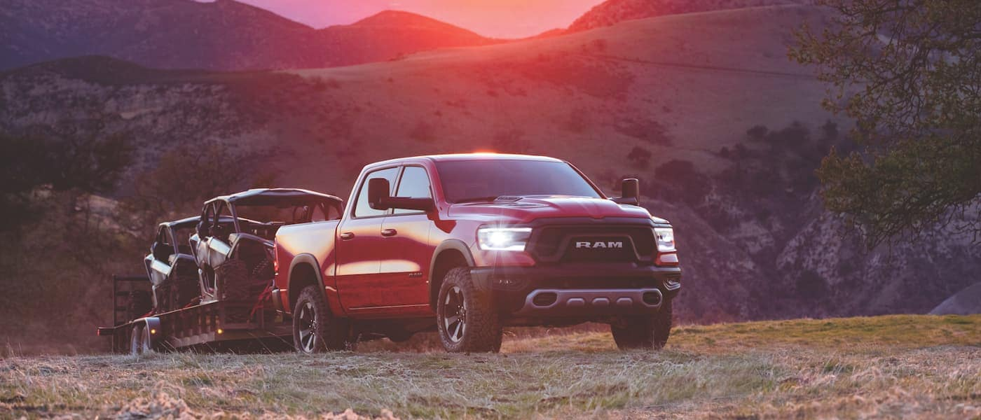 New Ram 1500 towing ATVs during sunset