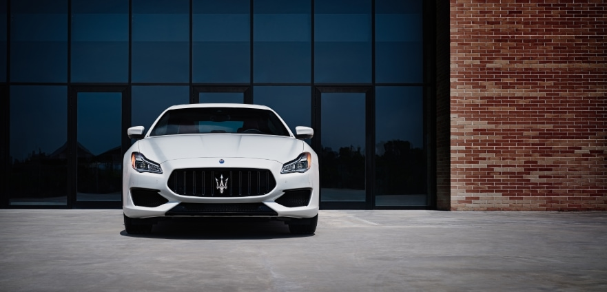 Maserati parked in front of a glass window