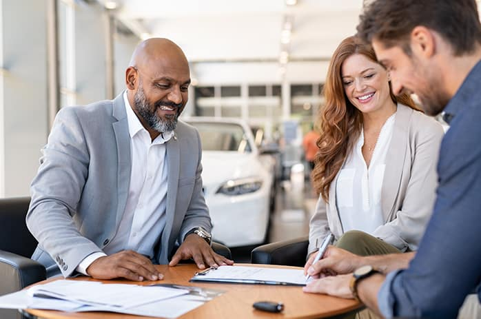 Leasing versus buying a vehicle at Mazda of New Bern in New Bern | Man signing document at a car dealership