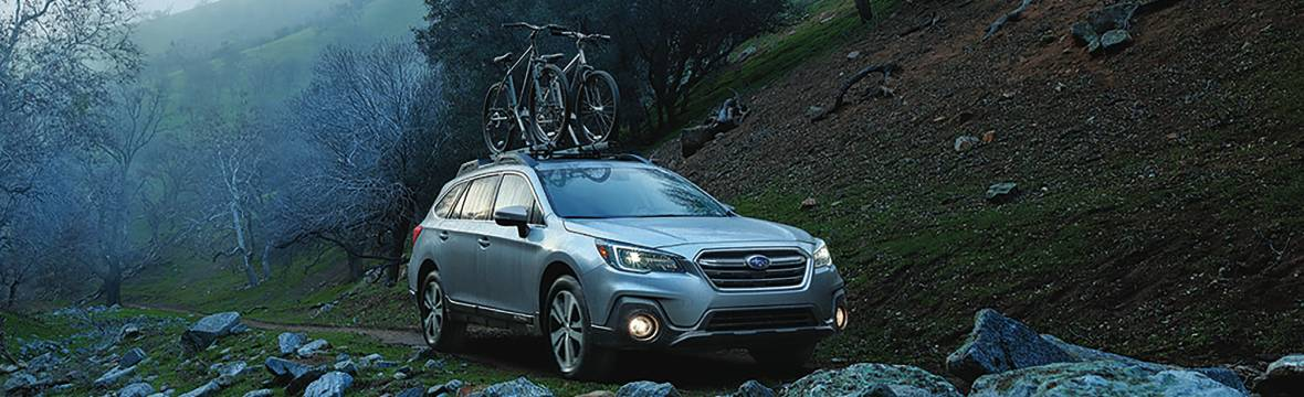 New Subaru Outback with bikes in the mountains