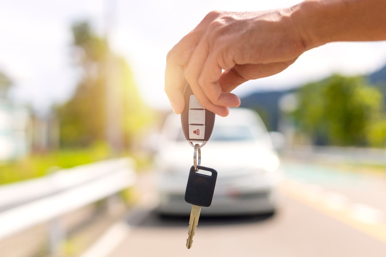 hands holding a pair of car keys in front of car