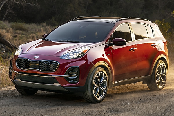 2020 Red Kia Sportage parked in a woody area