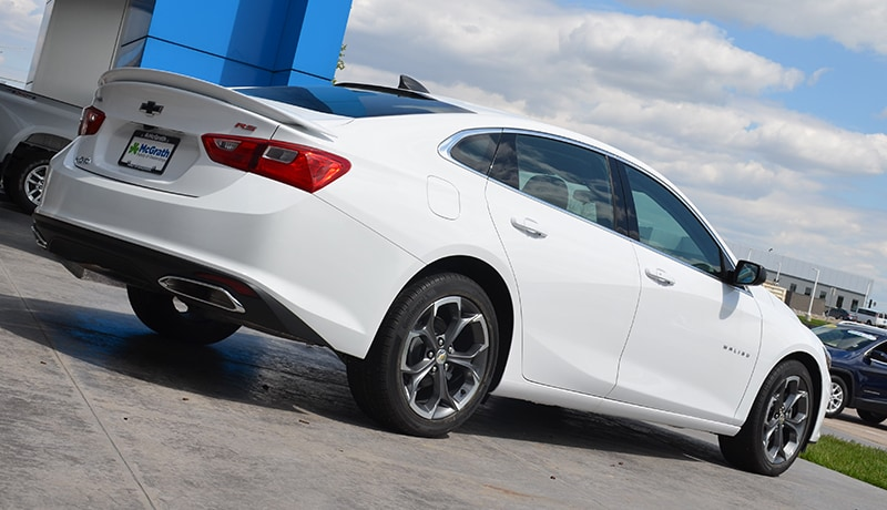 2019 Summit White Chevy Malibu RS rear tailgate parked in front of building