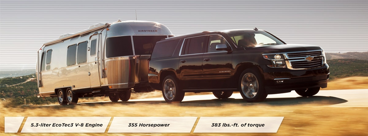 2019 Black Chevy Suburban Hauling a camper down an open road