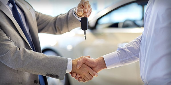 Car salesman shaking hands
