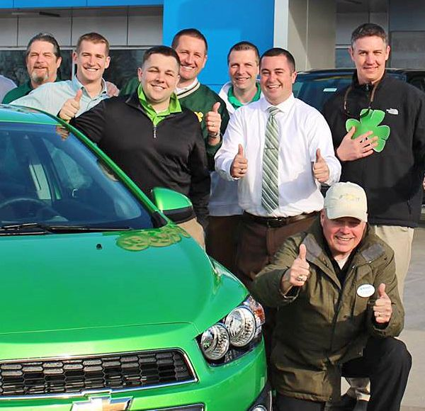 McGrath staff posing together by green car