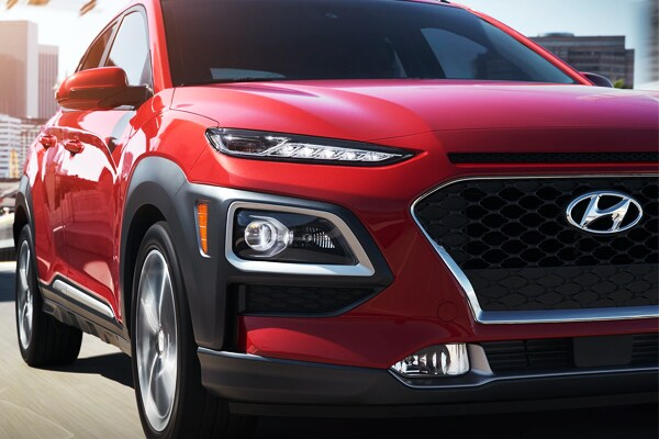 2019 Red Hyundai Kona Driving down the city block