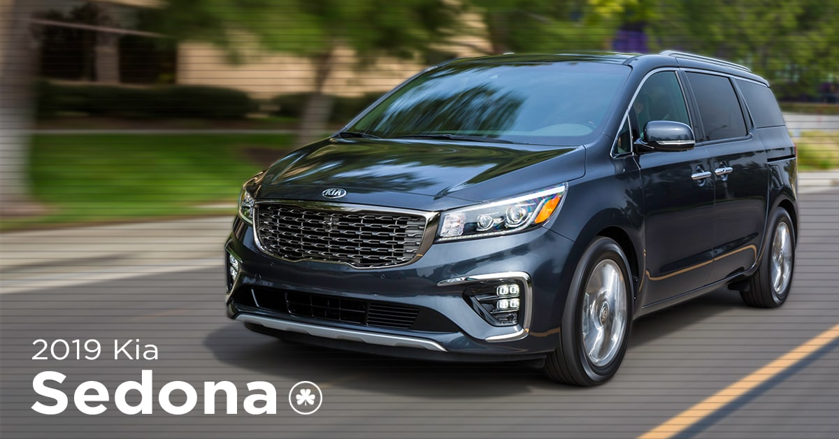 2019 silver Kia Sedona driving down the street