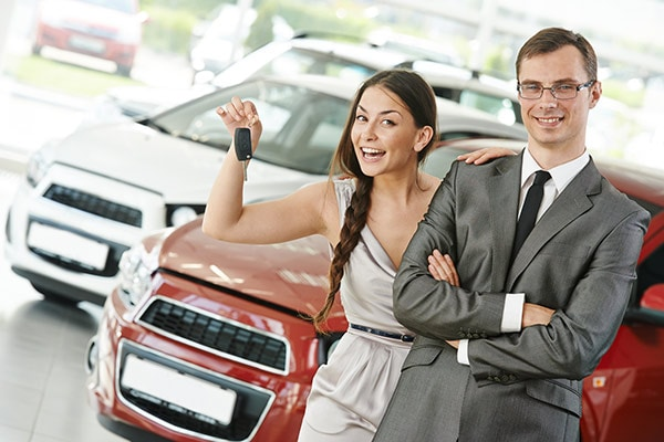 Woman holding keys and salesman