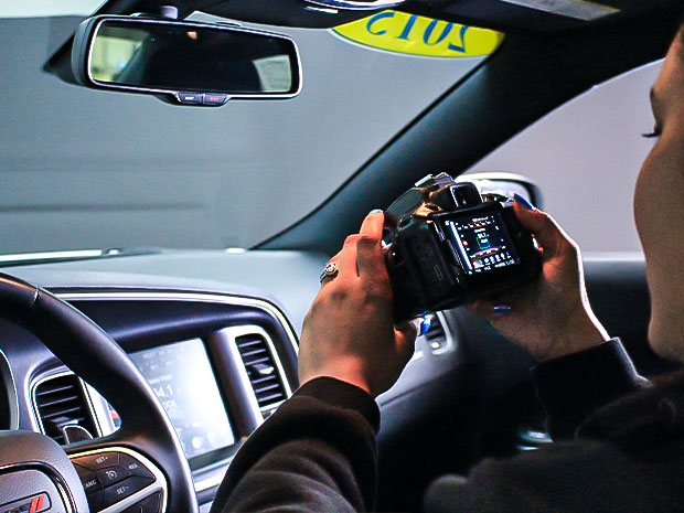 Young woman holding camera in car