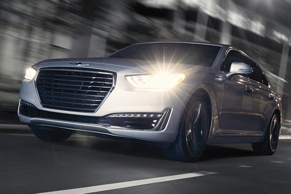 2019 Genesis G90 driving down the road with lights on