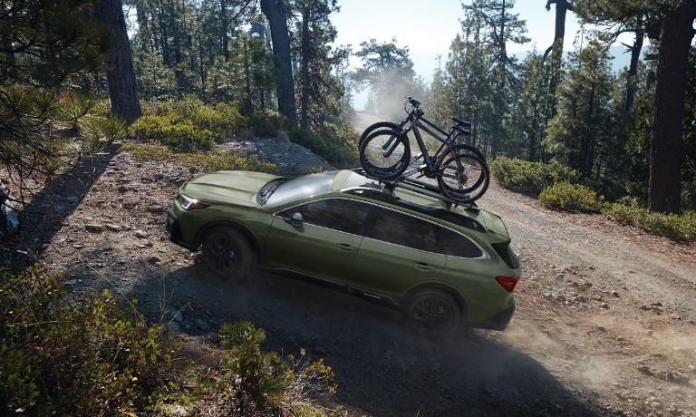 Green 2020 Subaru Outback on cliff