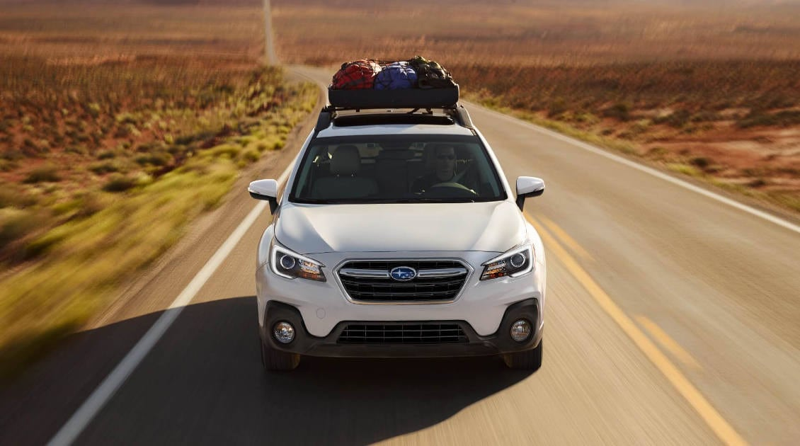 A white 2018 Outback 3.6R driving towards the viewer
