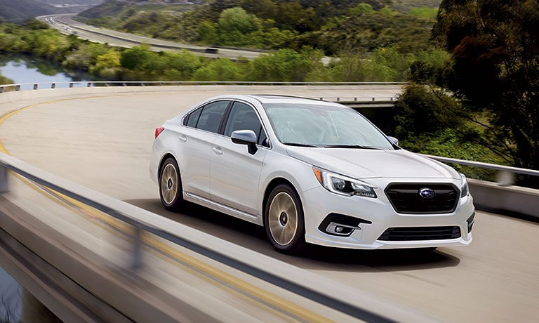 White 2019 Subaru Legacy driving down hill