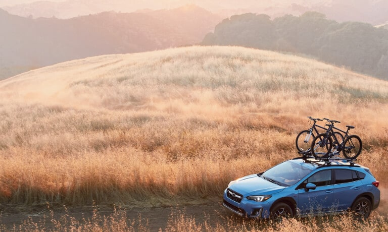 2020 Subaru Crosstrek in blue driving up dirt road in the in a open field view from above